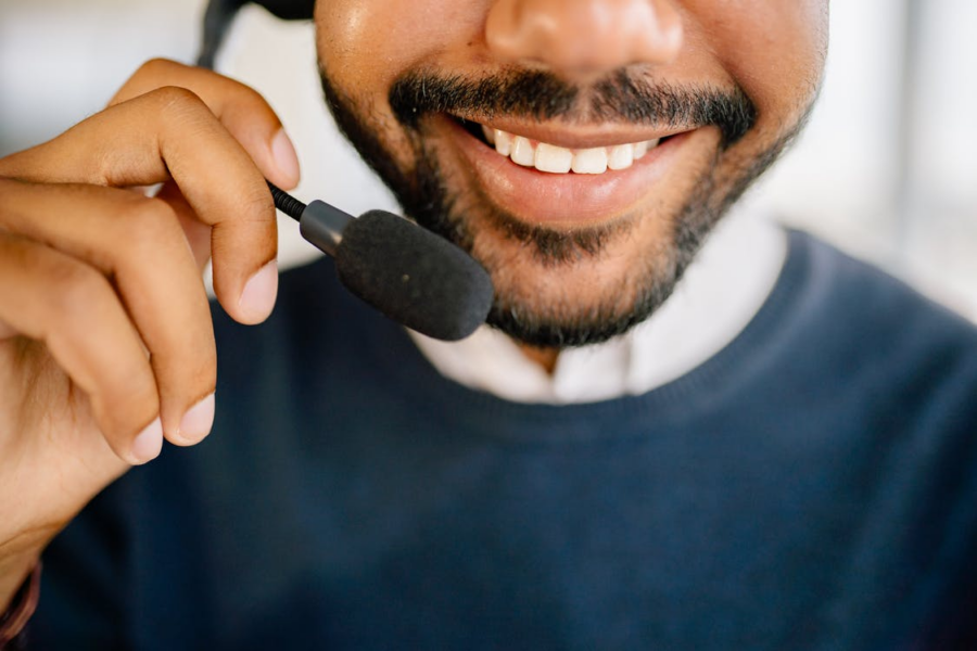 A medical contact center employee smiling while talking into his headset.